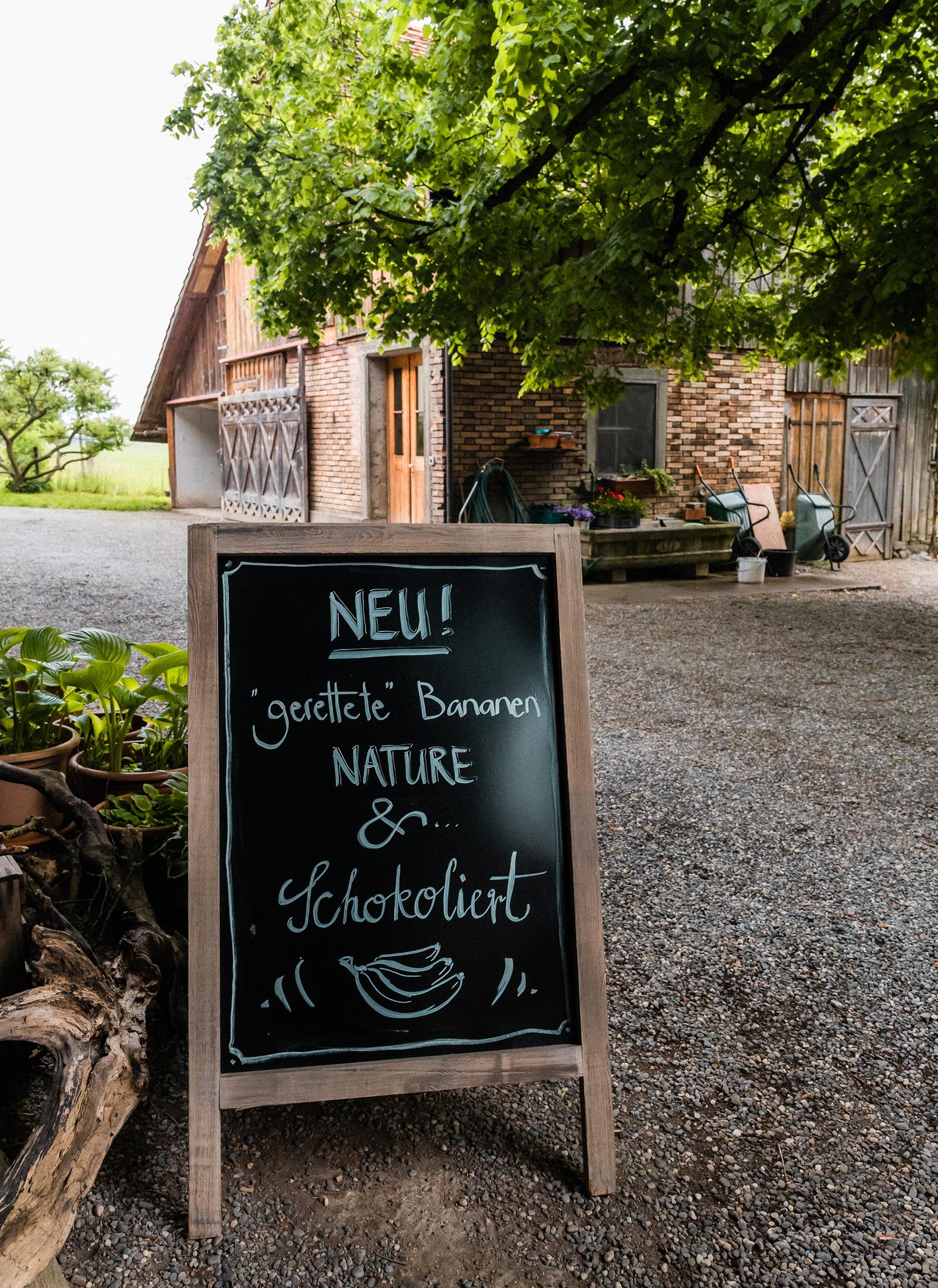 Schiefertafel vor dem Hofladen mit der Aufschrift: Gerettete Bananen nature & schokoliert